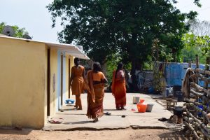Women walk outside of their tiny homes in Wajalabad, one of the most impoverished colonies Rising Star supports.